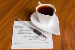 Coffee cup with handwriting project chart on napkin Stock Image