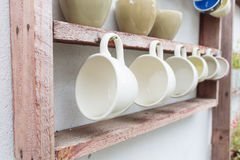 Coffee cup hanging on wooden shelf Royalty Free Stock Images