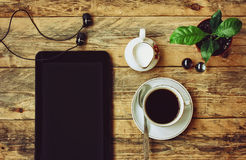 Coffee cup, headphones, flower pot, tablet, jug of milk Royalty Free Stock Photography
