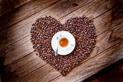 Coffee cup on heart form coffee beans Stock Images