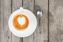 Coffee cup with heart shape on foam at wood table Stock Images