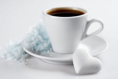 Coffee cup with heart shaped candy and snow hill Royalty Free Stock Photos