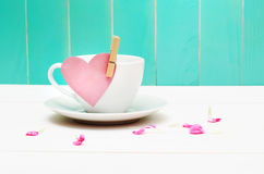 Coffee cup with heart tag. And flower petals over blue green wooden wall Stock Photo