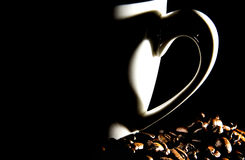 Coffee cup with herat shadow and coffee beans Royalty Free Stock Photos