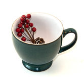 Coffee Cup With Holiday Floral Spray. Green pottery coffee cup filled with a holiday floral spray decoration on a white background stock photography