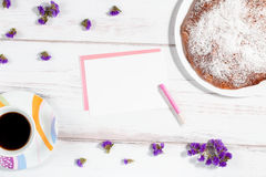 Coffee cup, homemade cake and paper on a white rustic wooden background Royalty Free Stock Photo