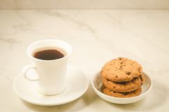 Coffee cup and homemade cookies with chocolate/coffee cup and homemade cookies with chocolate on a marble background, selective. Focus white biscuits food cake royalty free stock images