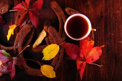 Coffee cup, horseshoes and leaves. Flatlay arrangement of cup of coffee, rusty horseshoes and autumn leaves on wooden surface. High angle shot of colorful fall Royalty Free Stock Photos