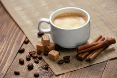 Coffee. Cup Of Hot Beverage. Close Up Of Mug Of Hot Drink With Coffee Foam Near Brown Sugar Cubes, Spice And Coffee Beans On Wooden Table. High Resolution Royalty Free Stock Photography