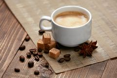 Coffee. Cup Of Hot Beverage. Close Up Of Mug Of Hot Drink With Coffee Foam Near Brown Sugar Cubes, Spice And Coffee Beans On Wooden Table. High Resolution Stock Image