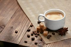 Coffee. Cup Of Hot Beverage. Close Up Of Mug Of Hot Drink With Coffee Foam Near Brown Sugar Cubes, Spice And Coffee Beans On Wooden Table. High Resolution Royalty Free Stock Image