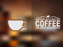 Coffee cup icon and text design with a blurred background. Royalty Free Stock Photo