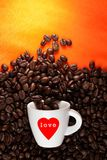 White coffee cup with love heart sign. Coffee cup with illustrated red love heart sign and with beans on the orange color background Royalty Free Stock Photo