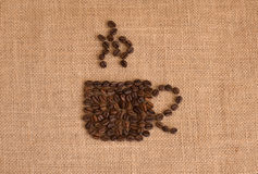 Coffee cup image made up of coffee beans on burlap background Stock Images