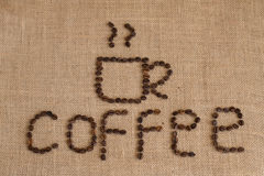 Coffee cup image made up of coffee beans on burlap background Royalty Free Stock Photo