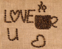 Coffee cup image made up of coffee beans on burlap background Royalty Free Stock Photos