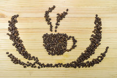 Coffee cup image made up of coffee beans on plank wood background Royalty Free Stock Photos