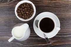 Coffee cup, jug milk and bowl with coffee beans. On wooden table. Top view Royalty Free Stock Photo