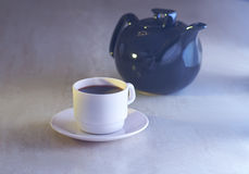 Coffee cup and kettle. In light on table Stock Images