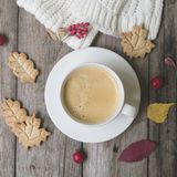 Coffee cup, knitted scarf, dry leaves, cookies, hawthorn and barberry fruitson a wooden background. Concept cozy atmosphere with a stock photography