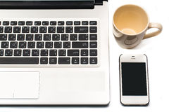 Coffee cup with laptop and cell phone isolated on white Stock Photos