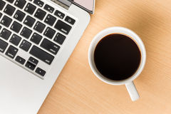 Coffee cup and laptop computer. On wooden background royalty free stock images