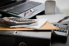 Coffee cup, laptop, Document file , pen , Calculator , notepad a. Closeup Coffee cup, laptop, Document file , pen , Calculator , notepad and glasses on wooden stock photo