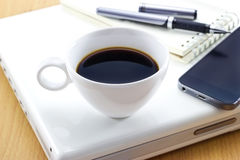 Coffee cup on laptop and mobile or pen with notepad for business Stock Images