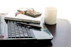 Coffee cup, laptop, pen , Calculator , notepad and glasses on wo Stock Photos