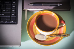 Coffee cup with laptop and pen on notebook Royalty Free Stock Photos