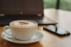 Coffee cup, laptop and smartphone on the wood table stock photo