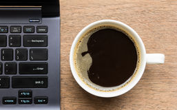 Coffee cup , laptop on wooden table Stock Image