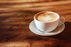 Coffee cup latte art in cafe. On wooden table royalty free stock photography