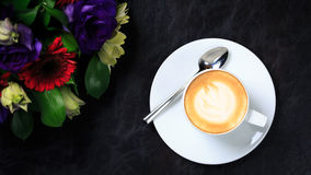 Coffee cup with latte art and flower bouquet. Concept of business event refreshment break. Top view. Black background. Horizontal, wide screen format royalty free stock images