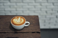 Coffee cup with latte art swan pattern on the wood table Royalty Free Stock Images