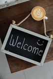 Coffee cup with latte art and the welcome sign on wood table.  Royalty Free Stock Image