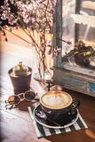 Coffee cup latte arts vintage mood. Sweet sepia retro light with old glass lamp, cactus; dried flowers on wood table Royalty Free Stock Image