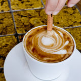 A coffee cup Latte being stirred by Cinnamon sticks. Stock Photography