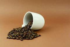 Coffee cup laying with coffee beans on brown background.  Royalty Free Stock Photos