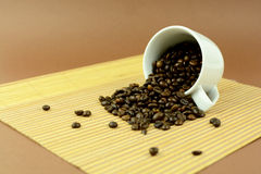 Coffee cup laying with coffee beans on placemat.  Royalty Free Stock Photography