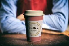 Coffee cup with a lid on a wooden bar with a blurry image of barista as background, 3d illustration. Royalty Free Stock Photography