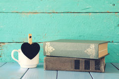 Coffee cup with little hart shape blank chalkboard and stack of old books on wooden table. vintage filtered Stock Photography