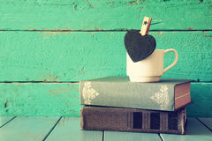 Coffee cup with little hart shape blank chalkboard and stack of old books on wooden table. vintage filtered and tones image Royalty Free Stock Photo