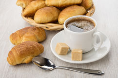 Coffee cup, lumpy sugar, croissants in wicker basket and spoon Royalty Free Stock Photo