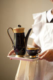 Coffee with a cup. Maid's hands holding a tray with a coffee pot and cup Royalty Free Stock Photos