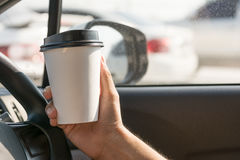 Coffee Cup. Man hand holding white paper cup of hot coffee in a car Royalty Free Stock Image