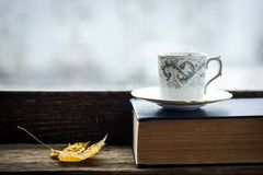Coffee cup  with maple leaf  and old book Royalty Free Stock Photo