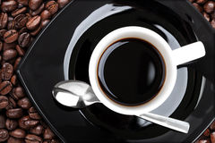 Coffee cup with metal spoon and beans Stock Images