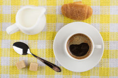 Coffee cup, milk jug, croissant, sugar and spoon on napkin. Coffee cup, milk in jug, croissant, sugar and spoon on yellow checkered napkin. Top view Royalty Free Stock Image