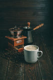 Coffee cup, mill and jezve on dark rustic table Royalty Free Stock Photography
